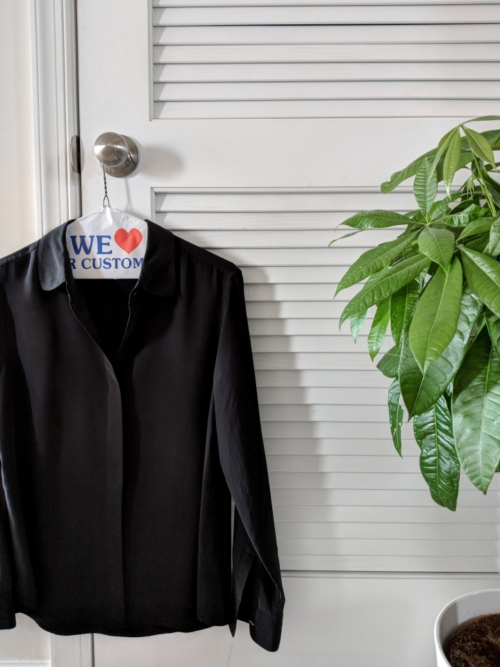 everlane silk blouse hanging from door