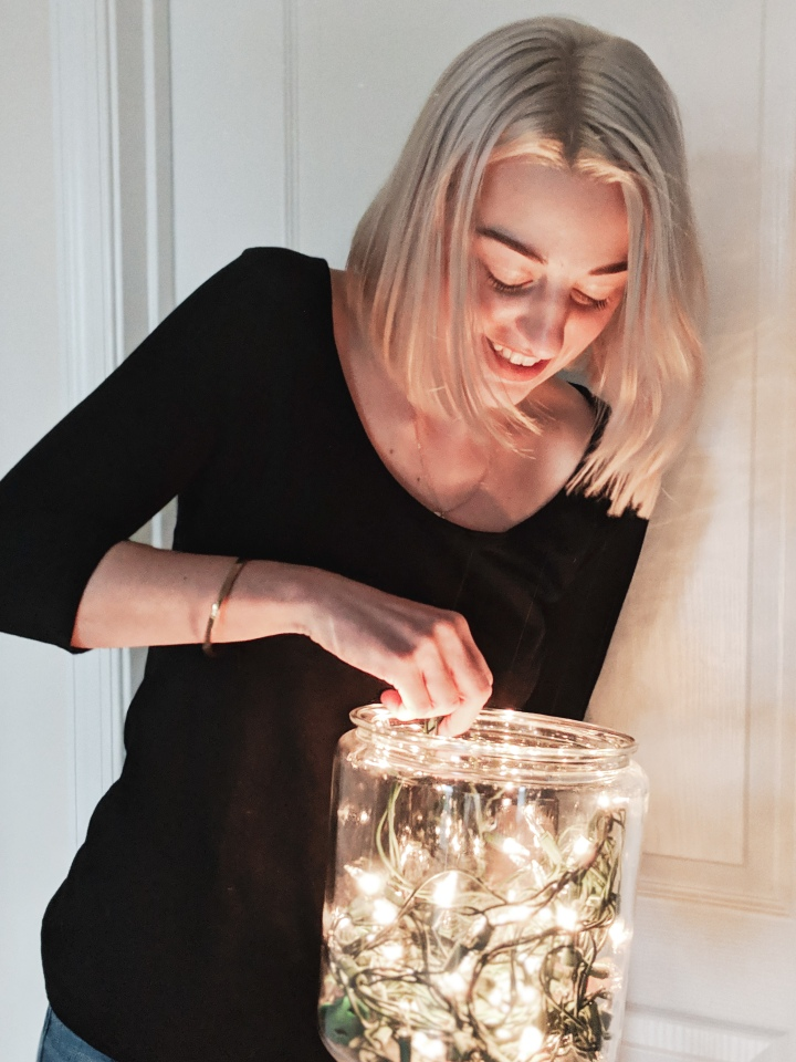 author with platinum blonde hair holding a jar of lights